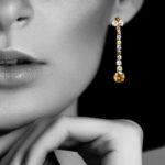 Model wearing colorful diamond pendant earrings
