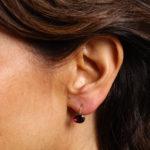 Model wearing stud portion of transformable garnet pendant earrings