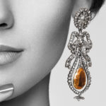 Model wearing antique imperial topaz and diamond pendant earrings