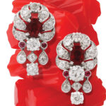 1930s pigeon blood ruby and diamond earrings with stacked red licorice background