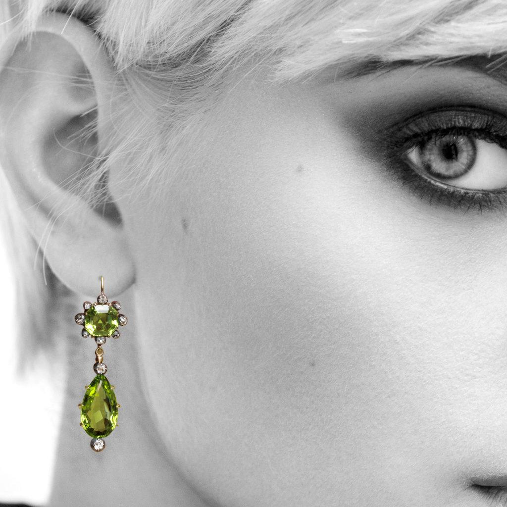Model wearing peridot and diamond pendant earrings