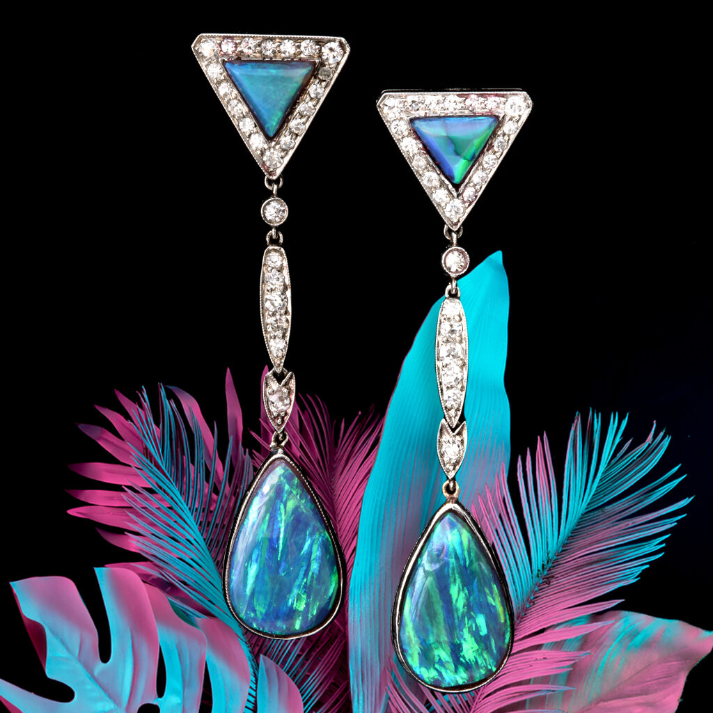 Black Opal and Diamond Earrings with black background and a blue and pink colored fern