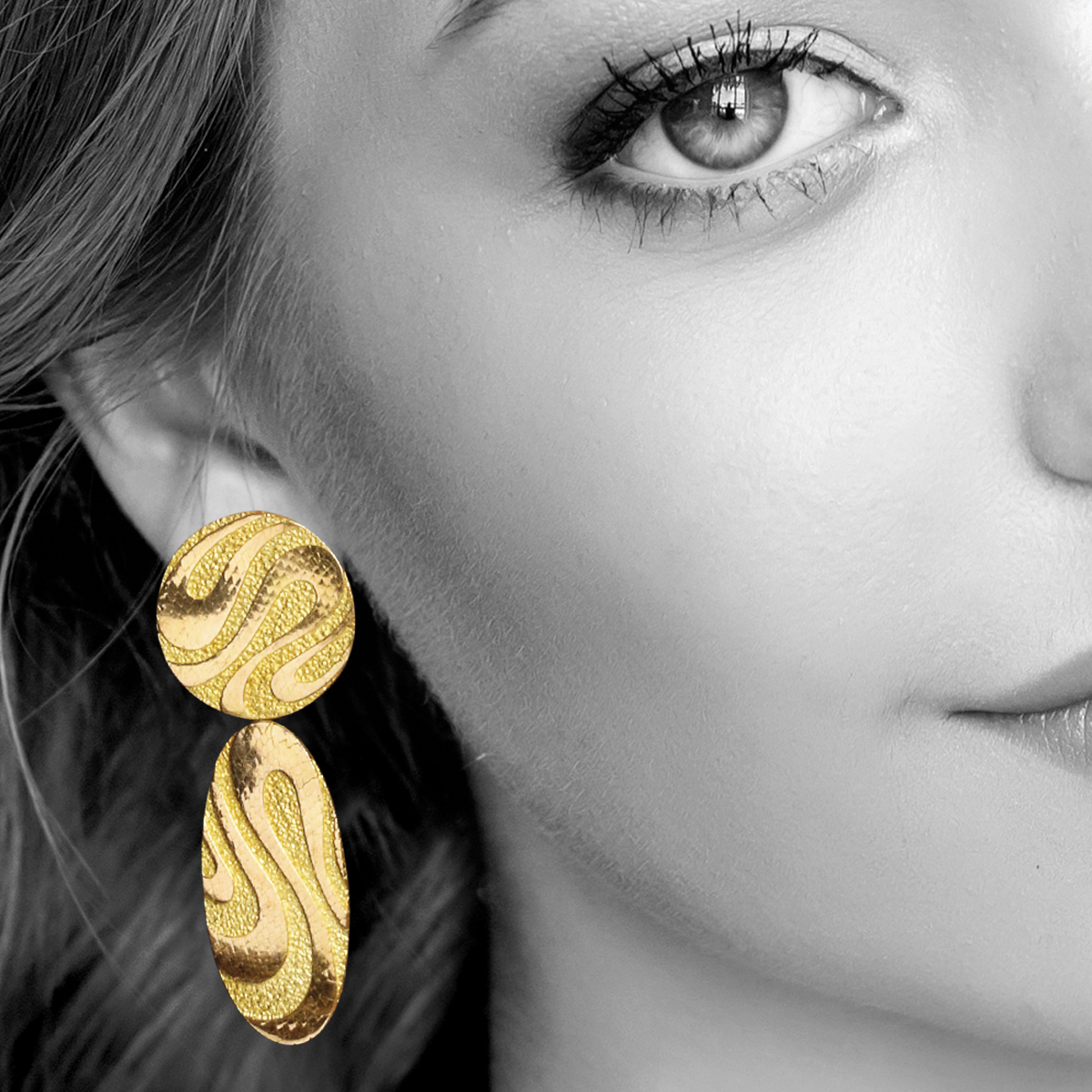 Model wearing gold pendant earrings by George L'Enfant