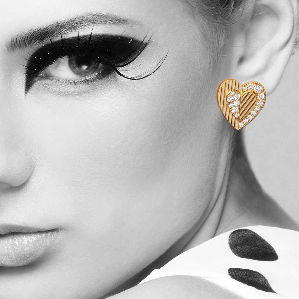 Model wearing gold heart shaped earrings with diamonds by Cartier