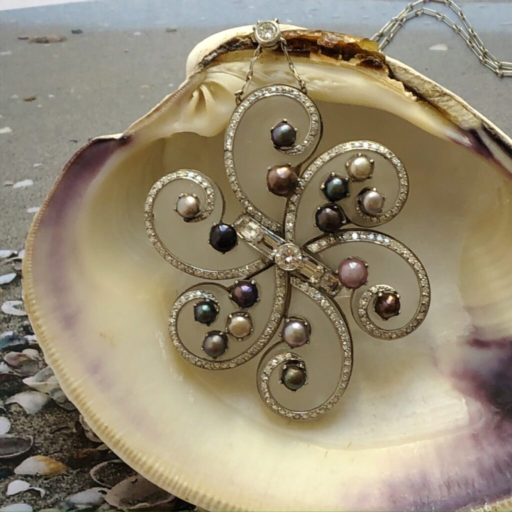 1960s Frosted Rock Crystal, Diamond, and Natural Pearl Pendant photographed in clam shell